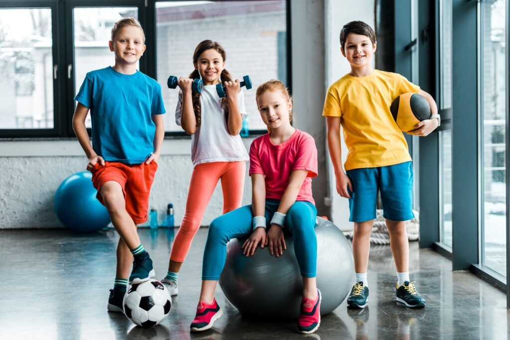 Laughing preteen kids posing with sport equipment